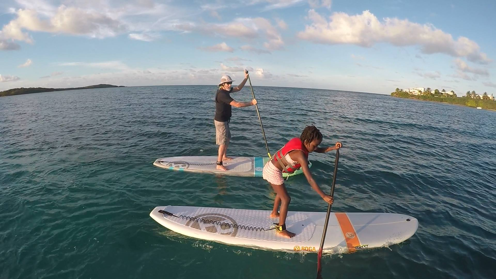 man and child using stand up paddleboards