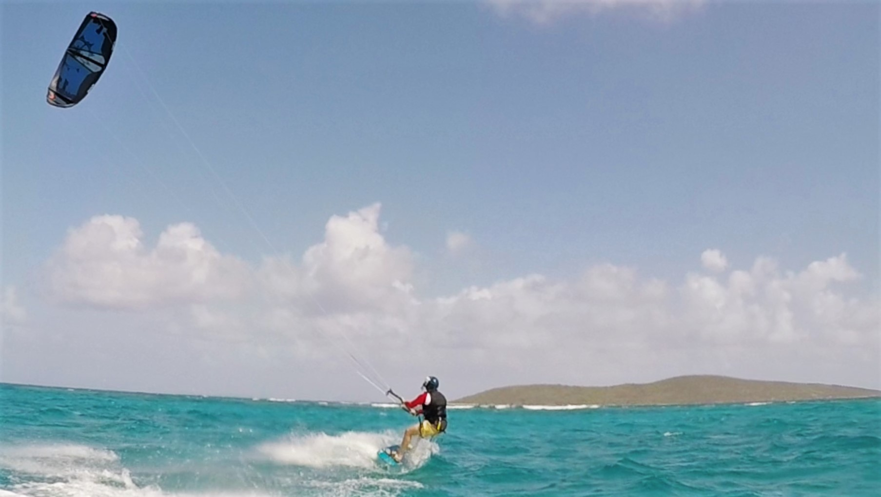Kiteboarder cruising through the caribbean sea