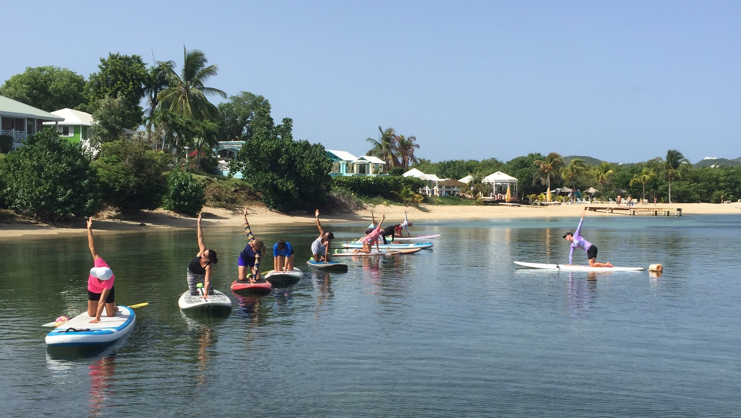 group of women doing yoga on stand up paddleboards, sup yoga class